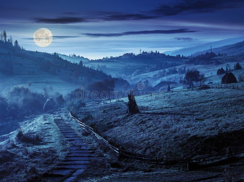 Moment - ner till byn i dimmiga berg på natten royaltyfri fotografi