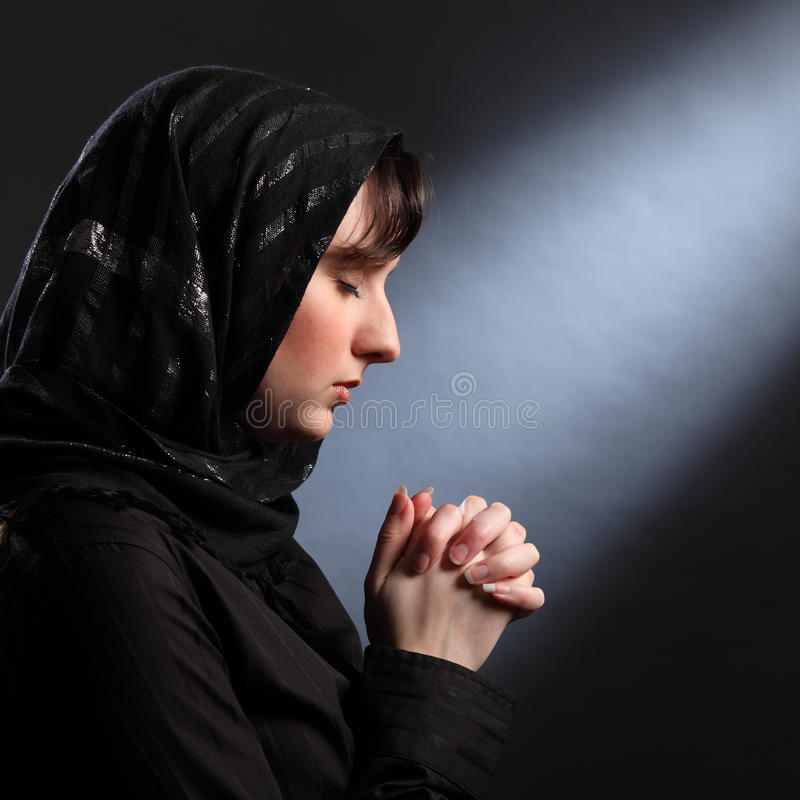 Moment of quiet faith as young woman prays stock photos