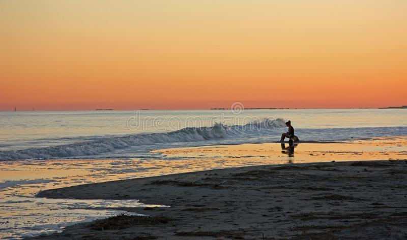 Moment of Reflection. One person finds solitude at sunset on an ocean beach stock photography