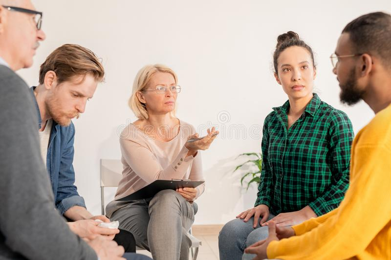 Moment of session. Mature blonde counselor pointing at one of patients while discussing his problem with the group stock photos