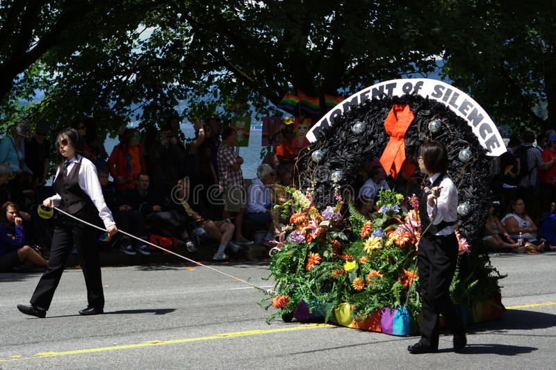 Moment of Silence, Vancouver Pride Parade. Two women escort a casket-shaped float covered in flowers and adorned with a red ribbon, to commemorate lives lost to royalty free stock photography