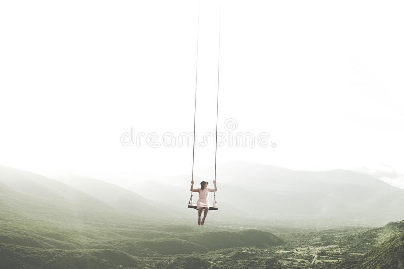 Moment surréaliste d'une femme ayant l'amusement sur une oscillation pendant du ciel photo stock