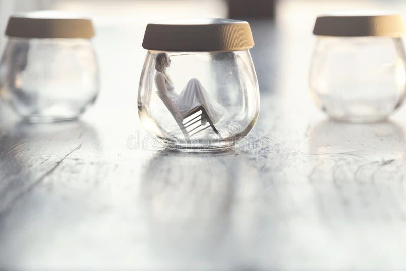 Moment surréaliste d'une femme minuscule s'asseyant sur une chaise à l'intérieur d'un vase en verre dans la table à la maison photographie stock