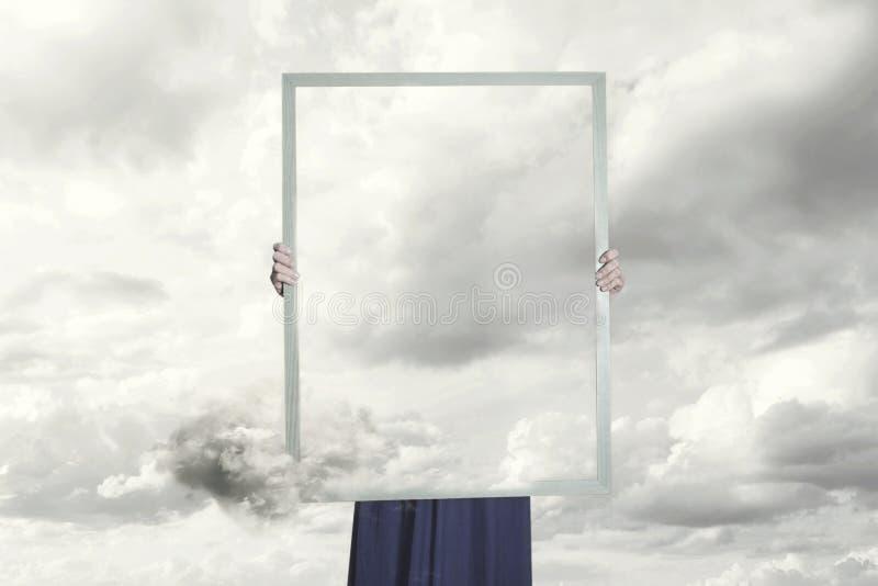 Moment surréaliste d'une femme se cachant derrière une photo des nuages égaux au paysage photos stock