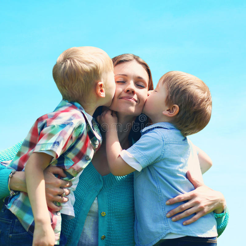 Moment szczęśliwa matka! Portret rodziny dwa dzieci synowie całuje mamy obraz stock