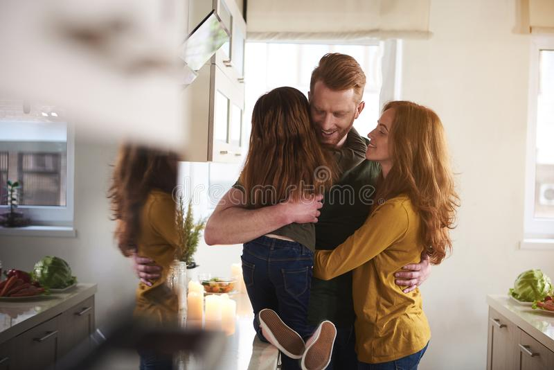 Mother and father coddling daughter in kitchen stock photos