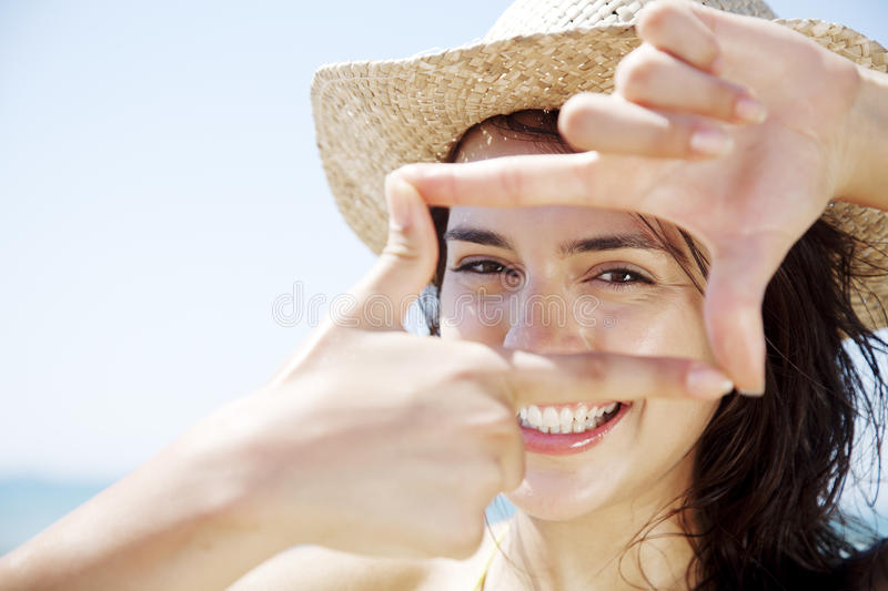 Moment in time. Young happy female looking through a frame made from her fingers stock images