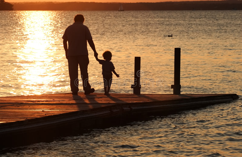 A Moment in Time. A father holds his son's hand as they walk out onto a dock at sunset