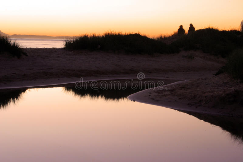 A moment in Time. Sunset over the sea with a couple sitting on a grassy dune with water from the previous day's high tide pooling behind them reflecting the royalty free stock image