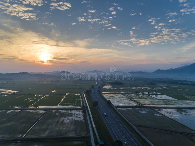 Momento aereo di alba con la vista della superstrada in mezzo alla risaia fotografia stock