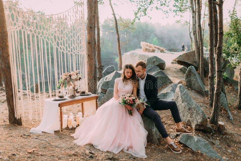 Momento atractivo de los recienes casados de los pares, feliz y alegre El hombre y la mujer en ropa festiva se sientan en las pie foto de archivo libre de regalías