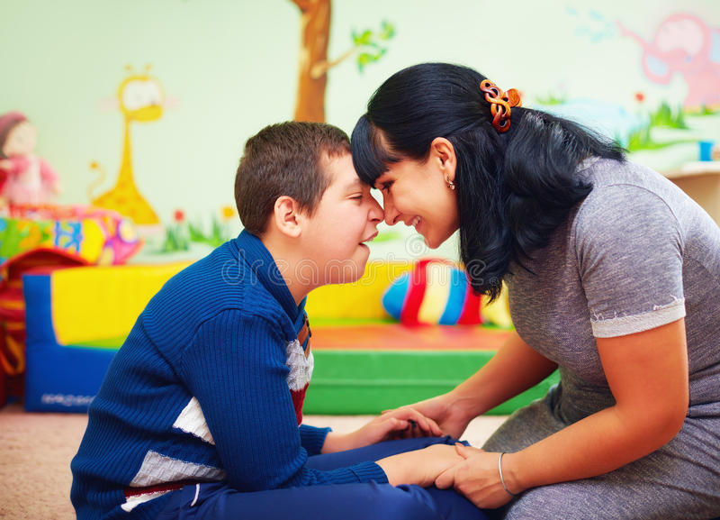 Momento com alma retrato da mãe e de seu filho amado com inabilidade no centro de reabilitação foto de stock