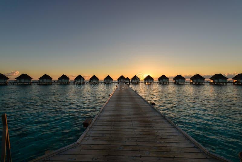 Momento de la puesta del sol en el centro turístico de lujo, calzada de madera para regar los BU del chalet fotografía de archivo libre de regalías