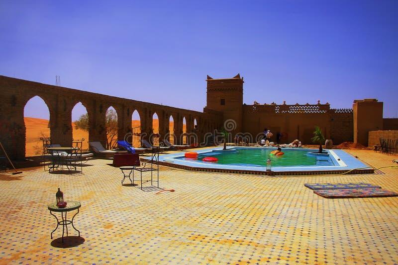 Momento de relajación en un desierto marroquí de los amids de la piscina del hotel, con las dunas de arena en el horizonte fotos de archivo