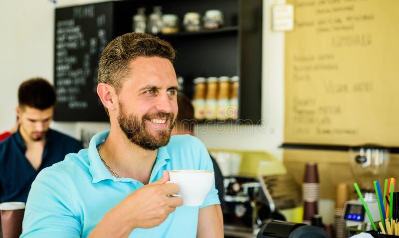 Momento della presa a cura circa voi stesso I bevitori del caffè vivono più lungamente Il tipo barbuto dell'uomo beve il fondo de fotografia stock libera da diritti