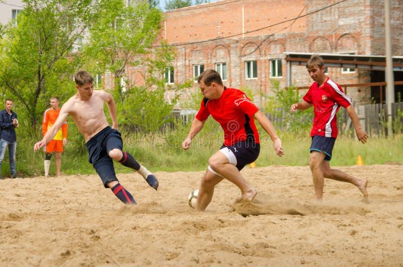 Momento do jogo no futebol da praia no campeonato amador entre m imagem de stock royalty free