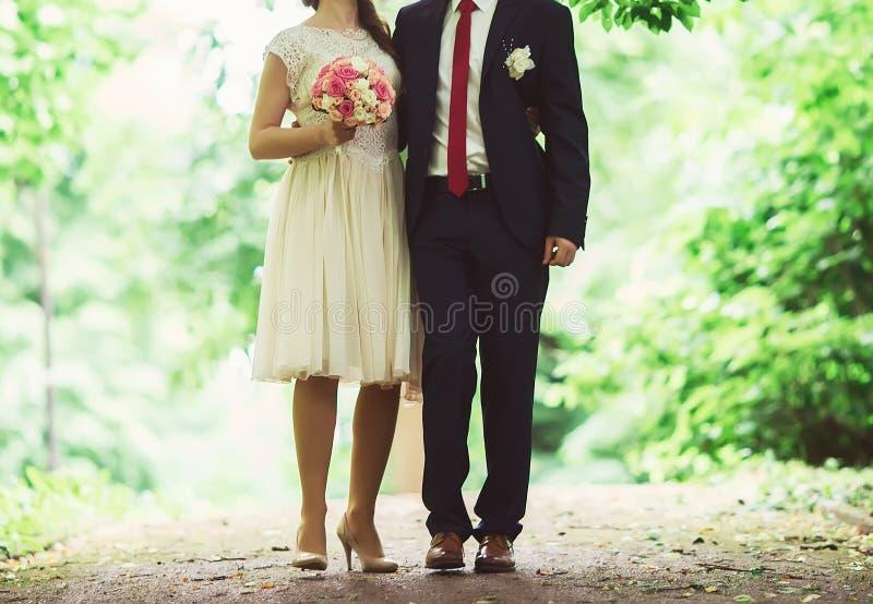 Momento en la boda, la novia y el novio llevando a cabo las manos con bouqu foto de archivo