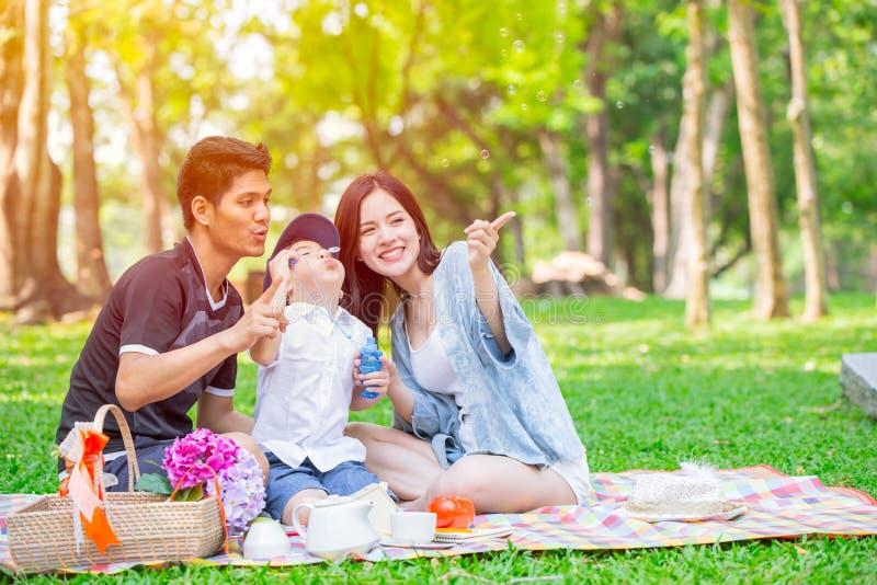 Momento feliz de la comida campestre del día de fiesta del niño adolescente asiático de la familia una en el parque imagen de archivo