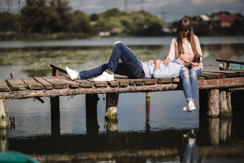 Momento ideale Belle giovani coppie che abbracciano e che sorridono mentre sedendosi sul pilastro immagini stock