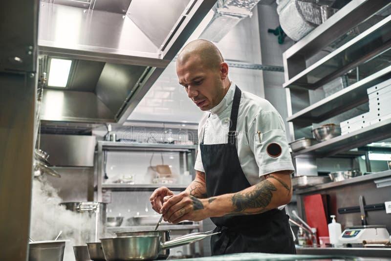 Momento importante Cozinheiro chefe profissional sério no avental, com diversas tatuagens em suas mãos cozinhando em uma cozinha  fotos de stock royalty free
