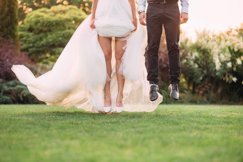 Momento parado, um pulo, salto no ar como se os noivos estão voando acima da grama verde no jardim, não imagem de stock royalty free