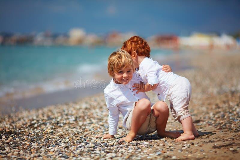 Momento sincero divertido de niño que coge a su pequeño hermano del bebé, cuando él ` s que cae, vacaciones de verano de la famil foto de archivo