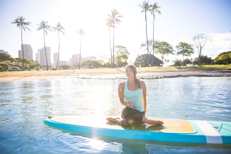 Momento soleggiato del chiarore del sole di mattina di una giovane donna graziosa in SUP Yo fotografia stock