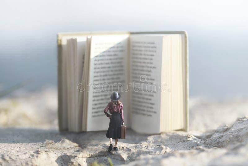 Momento surreale di una donna che cammina verso un libro gigante fotografie stock libere da diritti