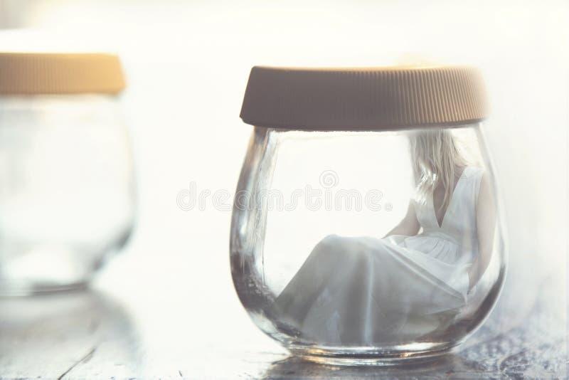 Momento surrealista de una mujer dentro de un tarro de cristal imagen de archivo