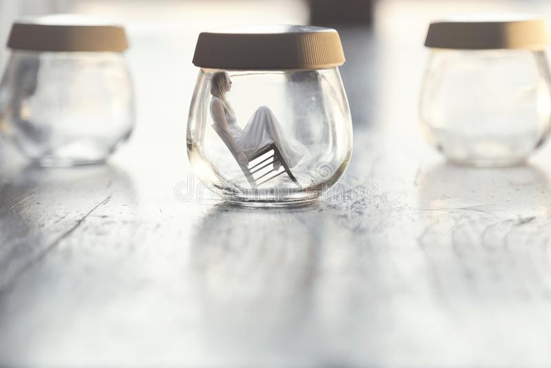 Momento surrealista de una mujer minúscula que se sienta en una silla dentro de un florero de cristal en la tabla en casa fotografía de archivo
