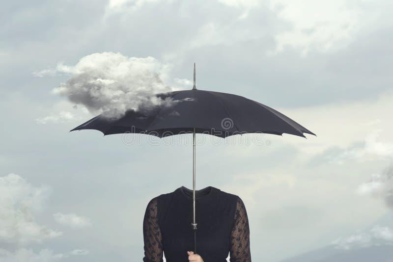 Momento surrealista de una nube que acaricia el paraguas de una mujer sin cabeza fotos de archivo libres de regalías