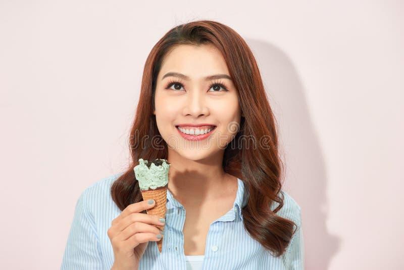 Momentos felizes doces da jovem mulher elegante atrativa que tem o divertimento com gelado do cone no fundo cor-de-rosa Sonho, de fotografia de stock
