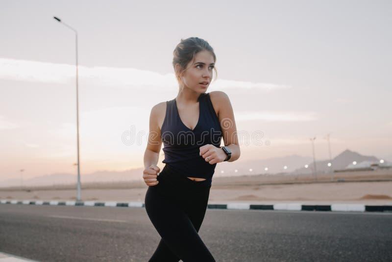 Momentos soleados felices de la mañana de mujer joven asombrosa motivada trabajadora en la ropa de deportes que corre en el camin imagen de archivo