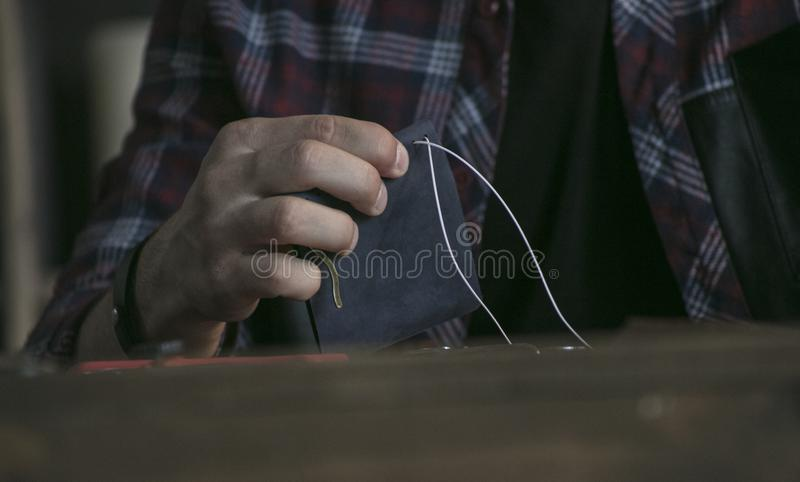 Close up of man hand leather maker holding wallet of blue color and sewing royalty free stock images
