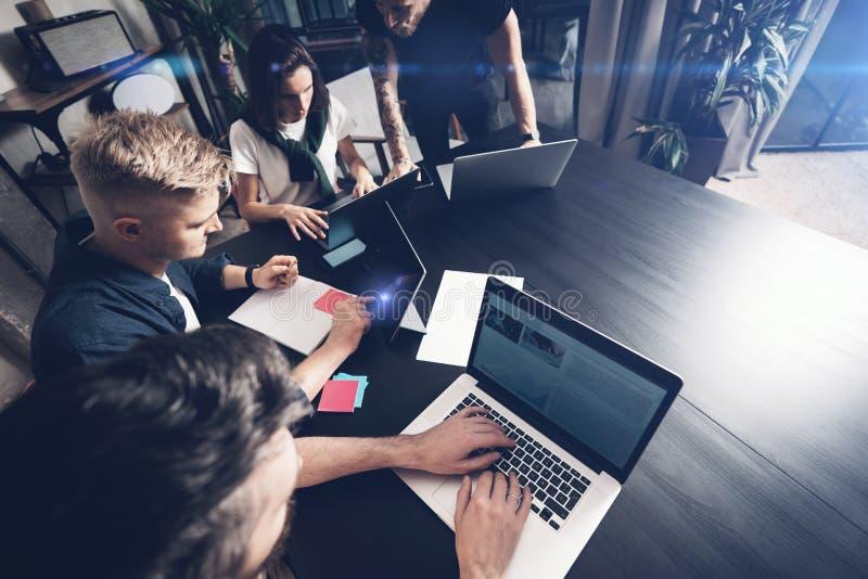 Moments fonctionnants Groupe de jeunes de collègues dans la tenue de détente futée discutant des affaires tout en travaillant dan photos stock