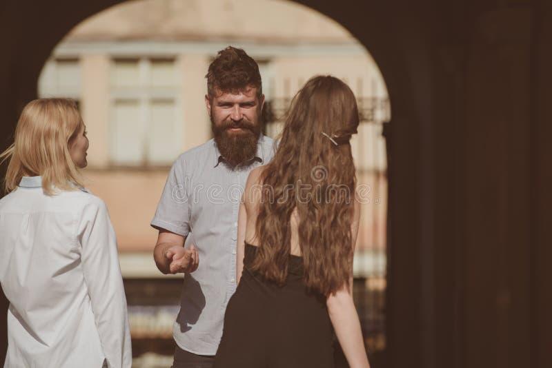 Moments heureux Homme barbu et jolies femmes souriant sur la rue Liens de l'amitié Amies de datation d'ami Les gens image libre de droits