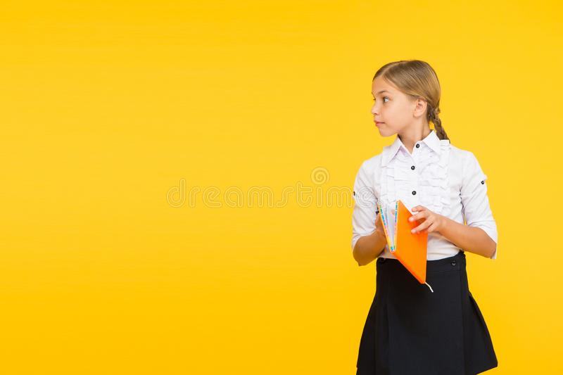 A moments of reading the best. Adorable little girl holding reading book on yellow background. Cute small schoolchild. Learn reading at primary school. A royalty free stock photography