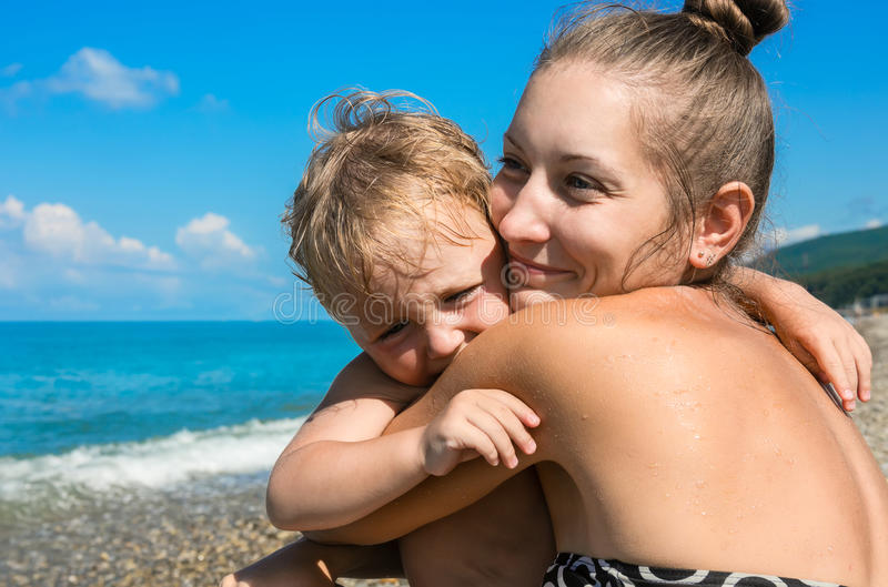 Momia con el pequeño hijo en la playa foto de archivo
