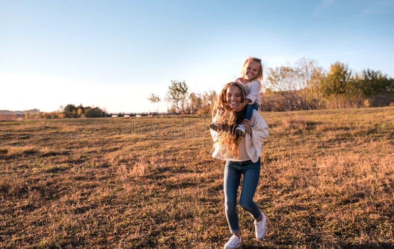 Momia e hija que se divierten junto al aire libre imagen de archivo