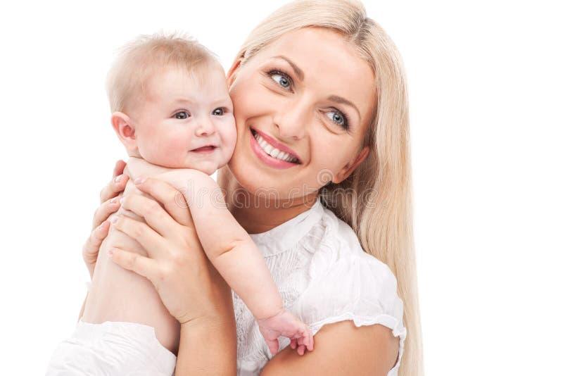 Momia joven que abraza al pequeño bebé bebé que se sostiene rubio hermoso y sonrisa imagen de archivo