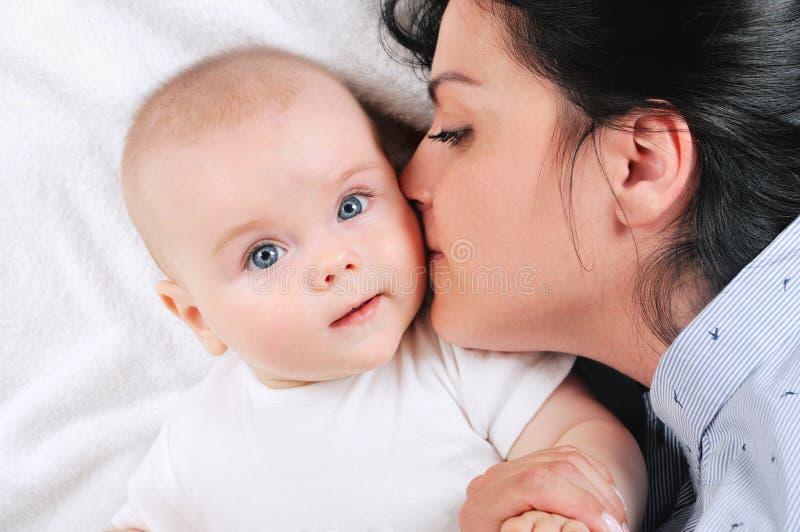 Momia que besa a su hijo en una cama blanca imágenes de archivo libres de regalías