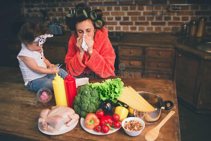 Momia subrayada en casa Madre joven con el pequeño niño en la cocina casera Mujer que hace muchas tareas mientras que se ocupa la imagen de archivo libre de regalías