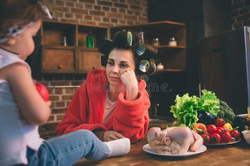 Momia subrayada en casa Madre joven con el pequeño niño en la cocina casera Mujer que hace muchas tareas mientras que se ocupa la imagen de archivo