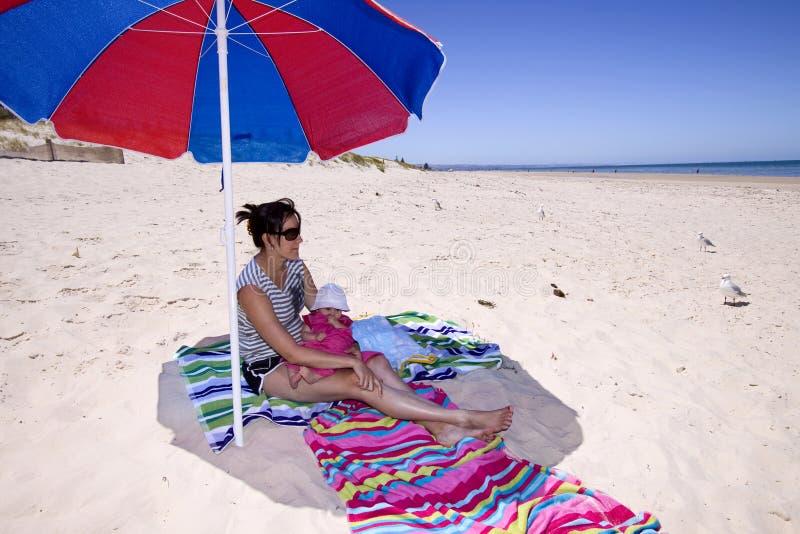 Momie et descendant à la plage photographie stock