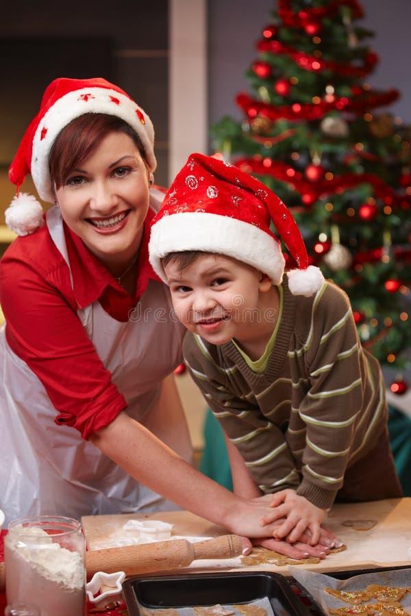 Momie et fils ayant l'amusement au traitement au four de Noël photos stock