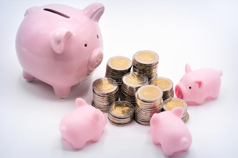 Mommy and baby piggy banks and pile of coins stock photography