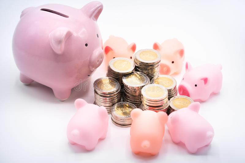 Mommy and baby piggy banks and pile of coins stock images