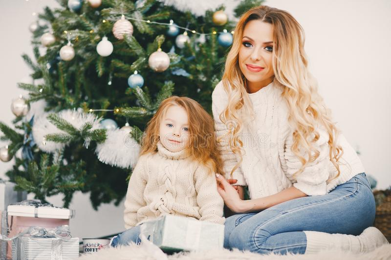 Mommy and daughter wrapping gifts. To put under the christmas tree stock photos