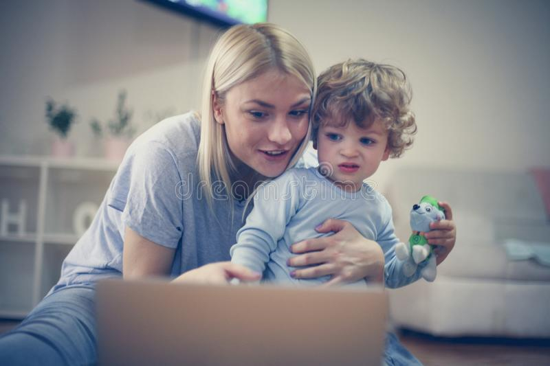 Mommy and me watch cartoons on laptop. Little boy. Childhood stock photo