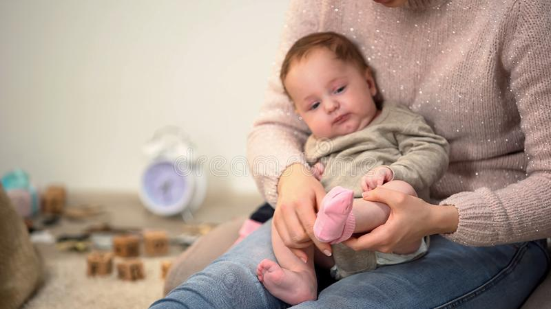 Mommy putting pink socks on adorable baby girl, newborn clothing and accessories stock photo